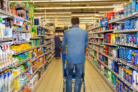 Bordeaux , Aquitaine / France - 03 30 2020 : Dos de l'homme marchant dans un supermarché avec panier Éditoriale