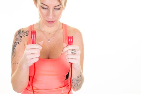 Attractive slim pretty smiling woman with jumping rope on neck with modern tatoo in arms Archivio Fotografico