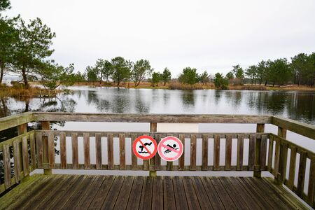 warning sign on wooden pier round white red sign no swimming and diving are forbidden