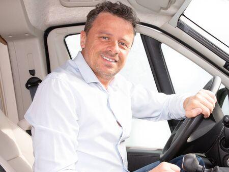 Happy young car driver behind steering wheel of van driving concept