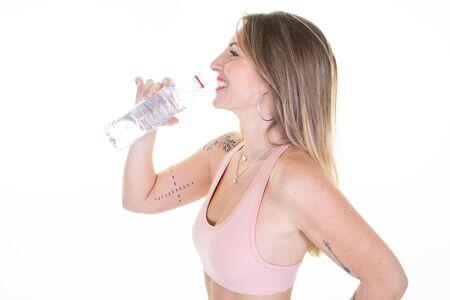 pretty slim tatoo sporty woman female athlete drinking water Archivio Fotografico