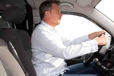 handsome profile of man in new van suv modern car driving on road