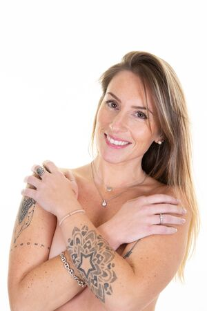 tatoo blonde smiling young woman standing topless with arms folded on her body posing in white background
