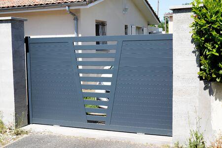 Portail de maison en aluminium de porte grise de porte moderne avec la rue de maison de banlieue de lames Banque d'images