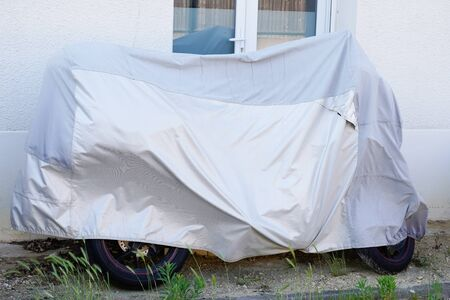 motorcycle street parked protected by silver protective cover grey motorbike tarpaulin jacket