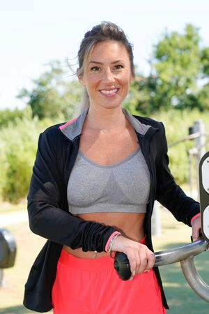 young blonde pretty woman using the outdoor gym equipment in sport park Фото со стока