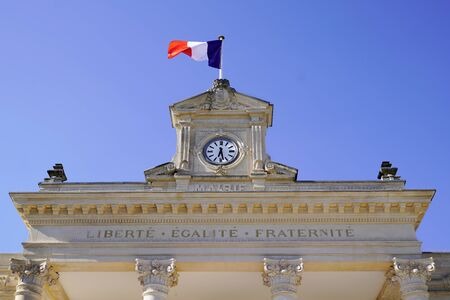 clock on city hall in France town with french flag in wind