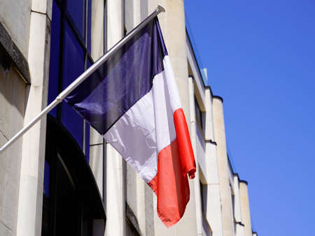French flag waving in front facade of city hall in town of france Stockfoto