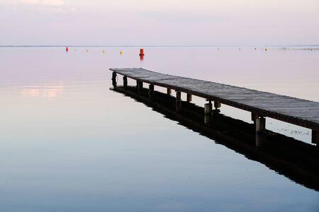 wood pontoon on morning sunrise on Lake Hourtin in Gironde france
