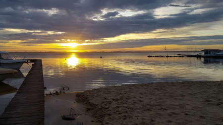 Sunset sanguinet lake in sunrise with sandy beach and wooden pontoon in landes france 版權商用圖片