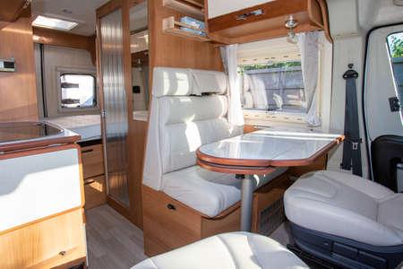 van modern white table and seat interior in luxury camper or motorhome on rv vanlife