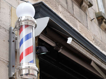 barber colored pole shop sign in vintage hairdresser wall with round white red blue colors Banque d'images