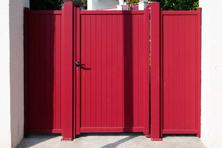red small modern metal aluminum gate of suburb house