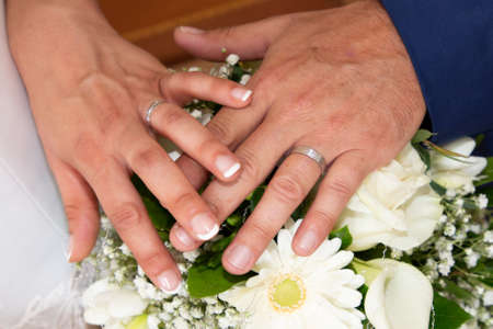 groom man and bride woman fingers hands with wedding rings over marriage bouquet flowers
