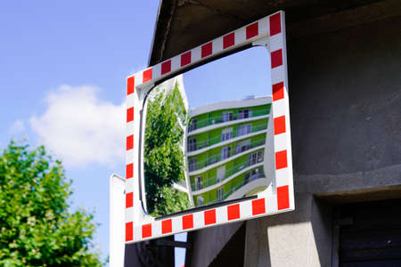 street traffic red white convex mirror in road safety concept in city center