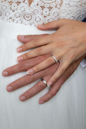 wedding rings on bride groom hands on white dress background