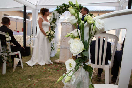 bride and groom blurry in summer wedding tent decorated for secular wedding ceremony