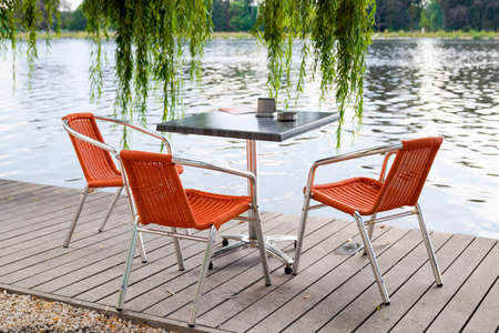 Outdoor small bar table on the wooden pontoon at the edge of the river Imagens