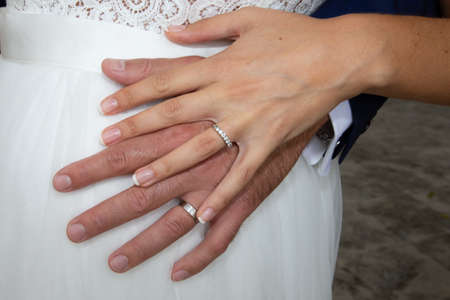 wedding rings on bride and groom hands on marriage white dress background Stock Photo