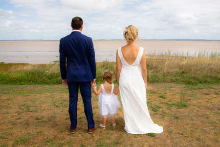 Happy wedding couple with child girl looking river coast in back view Stock Photo