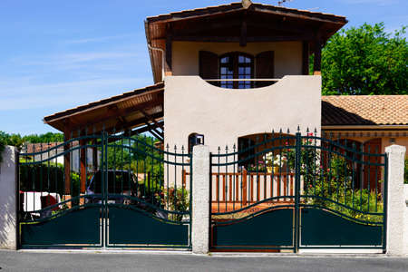 suburb home with two black dark metal aluminum gate slats portal access house door