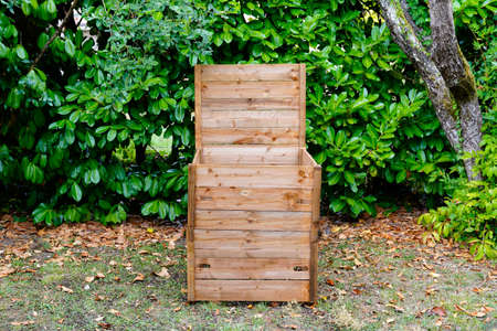 wooden open in home garden compost bin with organic material