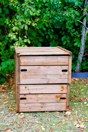 wooden closed home garden compost bin of organic material composter in back house outdoor Archivio Fotografico