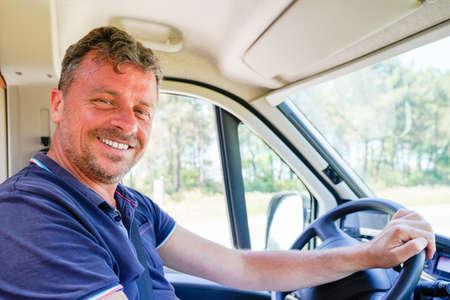 Happy man van driver behind steering wheel of car driving concept