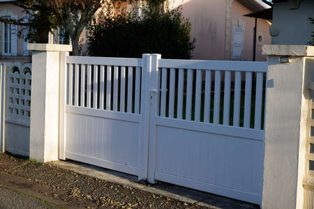 white gate aluminum portal to home access in street view