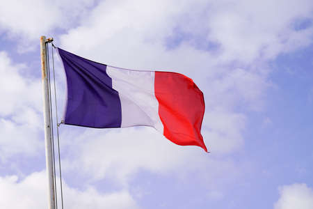 French flag of France wave over a blue cloud sky