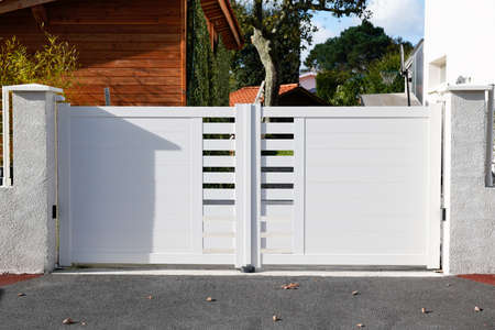 door white new metal driveway entrance gates portal in modern suburb house Stockfoto