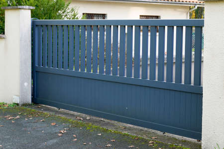 Metal gray driveway entrance slider gates house access garage in suburb