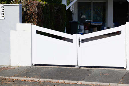 door large metal gate white fence on home suburb street access house garden Stockfoto