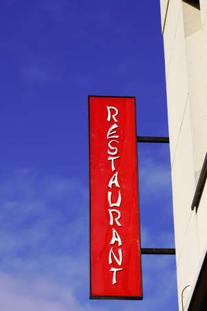 restaurant light red text sign on entrance building facade in street signboard