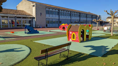 empty outdoors schoolyard school playground preschool building exterior with little house and bench Stockfoto