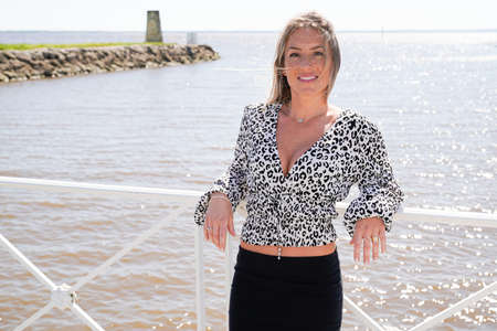 Outdoor cheerful portrait of beautiful young blonde woman smiling broadly and looking camera posing with water sea background