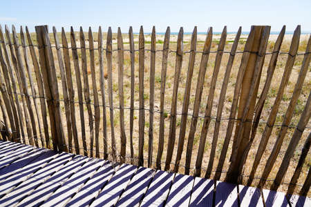 wooden protective barrier of the dune leading to the beach sea access walkway on atlantic ocean horizon in Jard sur Mer in france