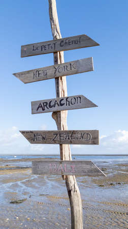 wood beach post with different wooden signboards pointing to various destinations in arcachon bay France