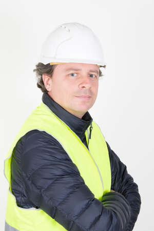handsome workman with helmet arms crossed yellow vest in white background