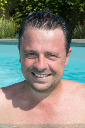 handsome middle aged man portrait in water swimming in outdoor pool