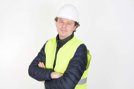 handsome man wearing construction helmet over white isolated background looking smiling on face