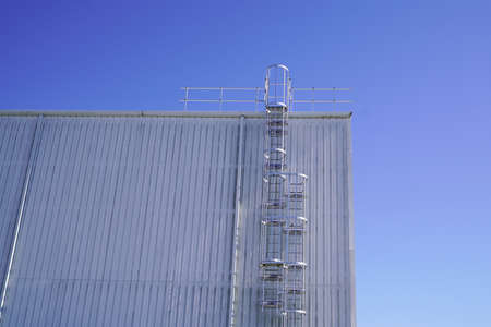 Ladder to the roof of a tall industrial building on blue sky background Zdjęcie Seryjne