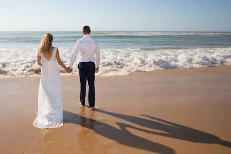 back view wedding couple walking on romantic sand sea beach