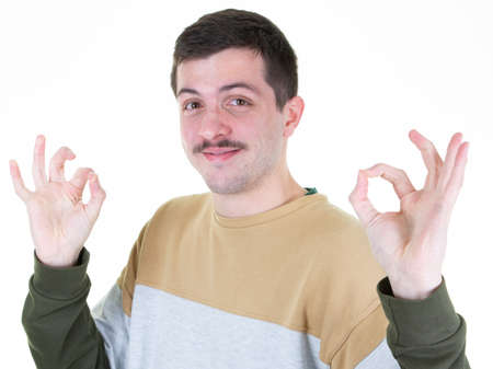 Portrait of handsome mustache man smiling and showing ok fingers sign at camera isolated over white background Foto de archivo