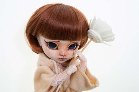 doll scary plastic with tears and flower in hands on white background