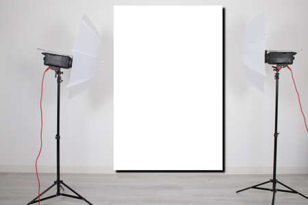 mockup empty room with blank white screen poster studio lights on tripod stands in Concept background with modern lighting equipment for professional photographer