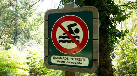 No bathing sign prohibited and risk of drowning text in french means bainade interdite risk de drowning on beach river