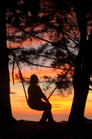 Silhouette of a lady sitting onn the swing during sunset photo