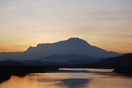 tuaran: Silhouette of Mount Kinabalu during sunrise seen from Megkabong bridge Tuaran Sabah Malaysia  image contains visible noise and blurry due to long exposure.