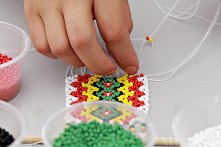 malaysian people: Working hand: demonstrating bead works of Kadazandusun beading crafts for costume accesories. Image contain visible noise and for background purposes only.